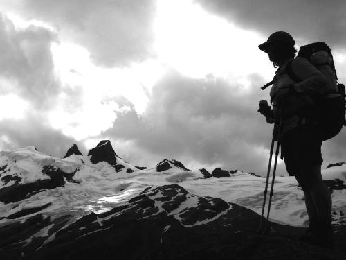 Silhouetted figure in front of glaciated mountains
